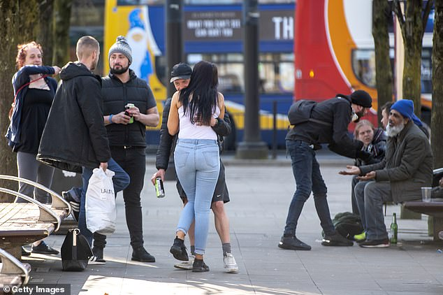 26399034-8155035-A_man_and_a_woman_embrace_in_Piccadilly_Gardens_in_Manchester_on-a-13_1585220096924
