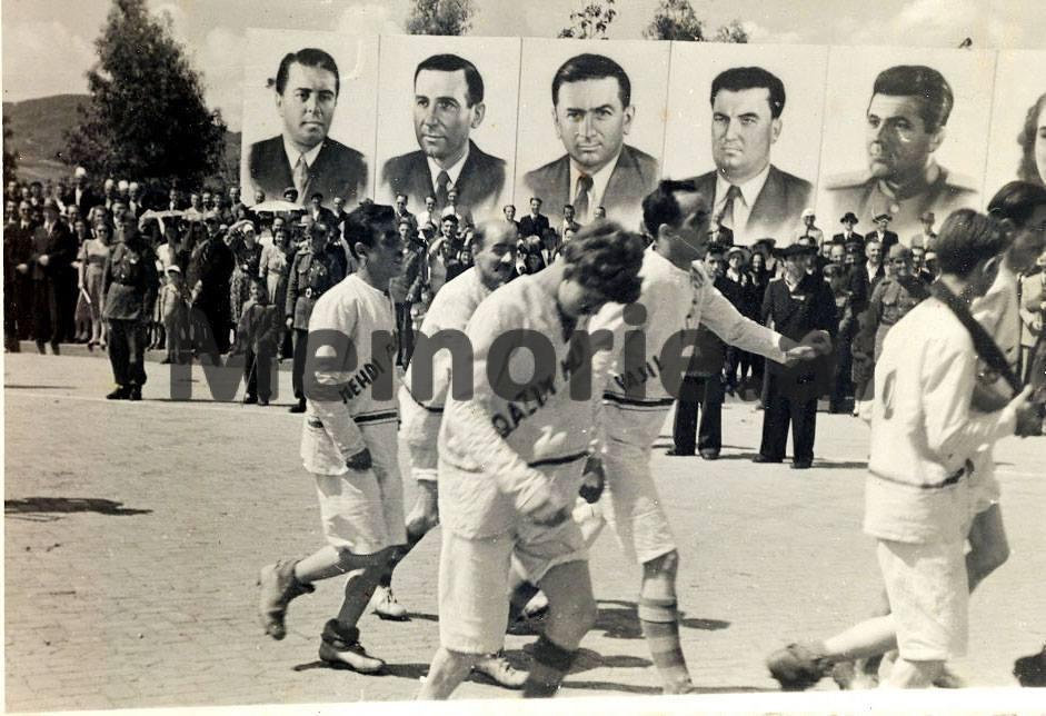 Eksponentet-kryesore-te-mergates-anti-komuniste-shqiptare-te-vene-ne-loje-nga-disa-qytetare-ne-Paraden-e-1-Majit-ne-Tirane.-Ne-sfond-oficeret-e-MPB-se-duke-qeshur.-1950