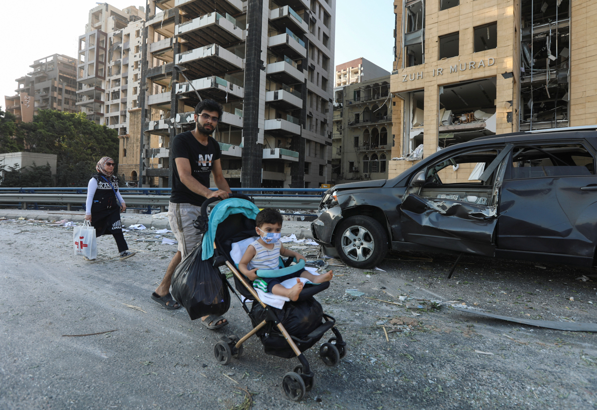 A man pushes a stroller with a child past a damaged vehicle near the site of Tuesday's blast in Beirut's port area